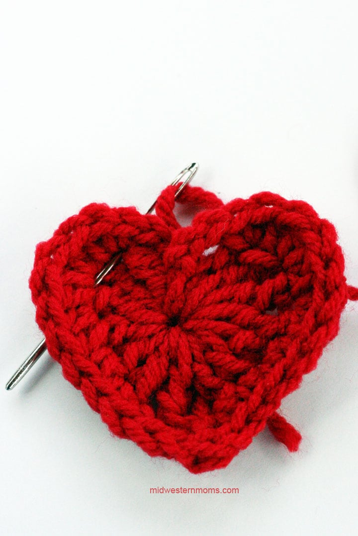 Step 2 in threading the larger heart onto the heart garland