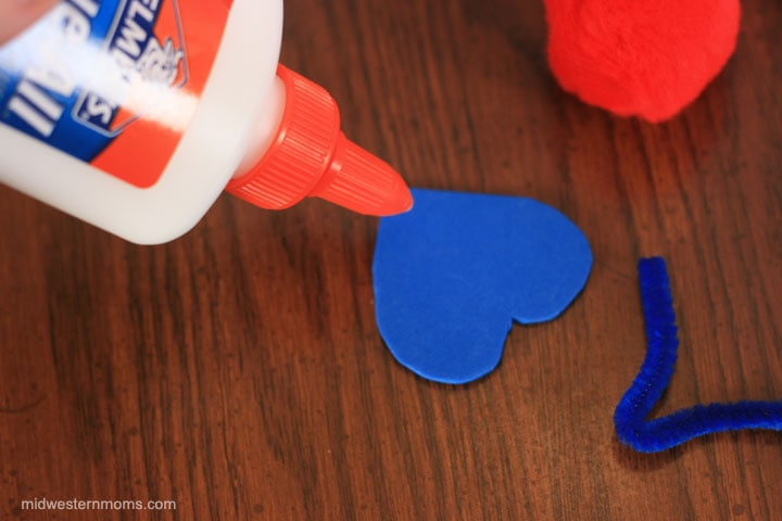 Adding glue to the heart to add the pom pom to make Valentine Love Bugs