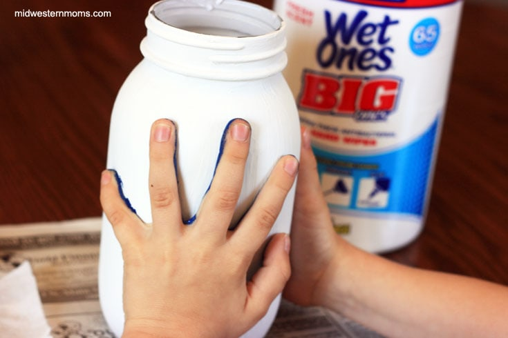 Place painted hand on jar to create a handprint