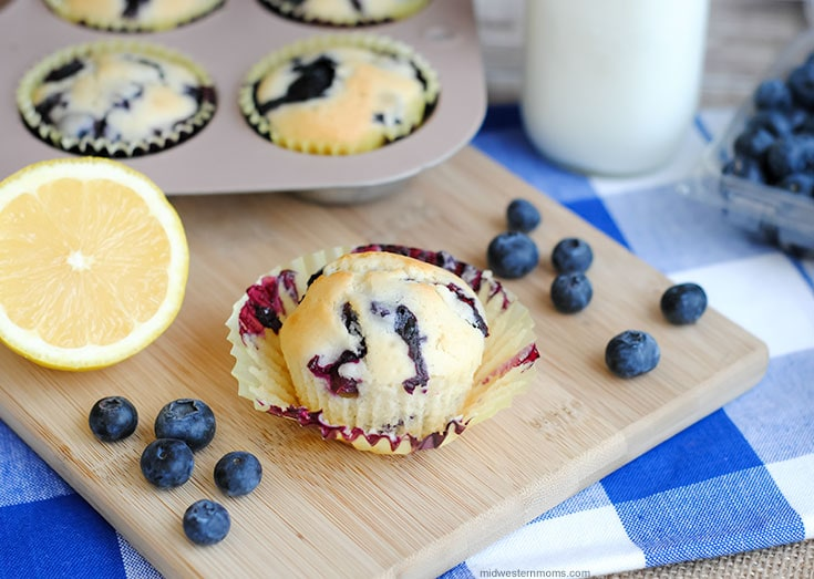 Lemon Blueberry Muffins with fresh lemons and blueberries scattered around and a glass of cool fresh milk.