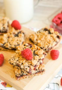 Raspberry Crumble Bars on a wooden cutting board with a glass of milk.