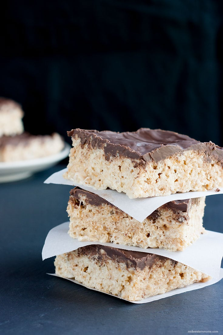 Three toffee rice krispie treats stacked with parchment paper between them. They are sitting on a slate board and the background is black.