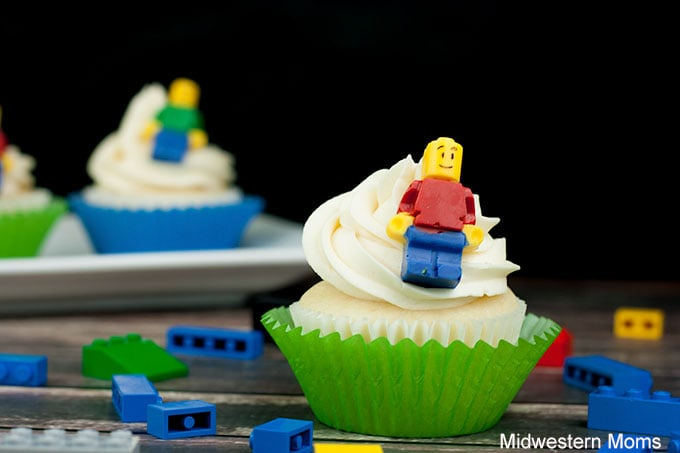 Lego cupcake on a table with real LEGOs around the table. The cupcake is a white cupcake with with buttercream frosting and topped with a Candy LEGO Mini-Figs.
