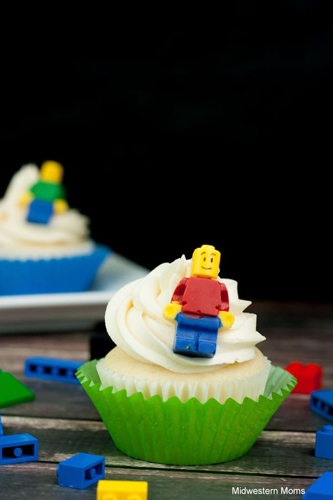 White cupcakes with white buttercream frosting topped with a Candy LEGO Mini-Fig! Lego cupcake has scattered LEGOs around it on the table.