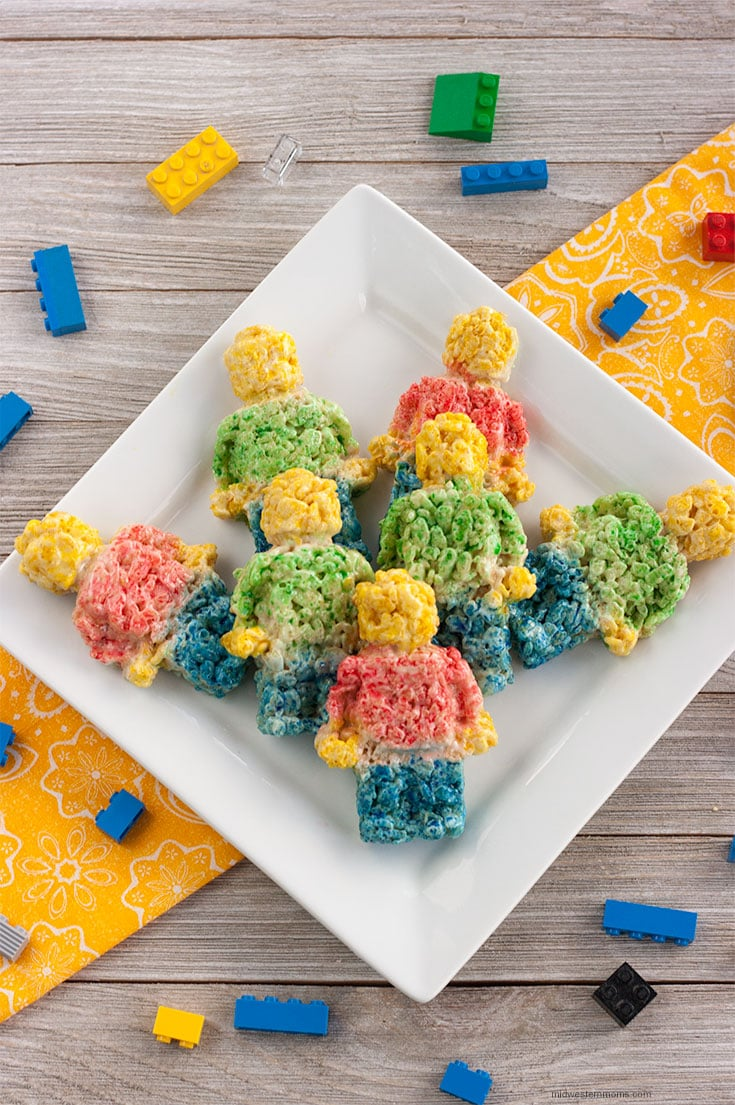 LEGO Rice Krispie Treats arranged on a white square plate. The table has scattered with real LEGOs.