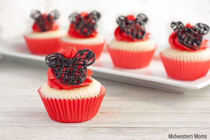 One Mickey Mouse cupcake in the foreground with a line of four more cupcakes behind it. These Mickey Mouse Cupcakes consist of a white cupcake, topped with homemade red buttercream frosting and candy Mickey ears.