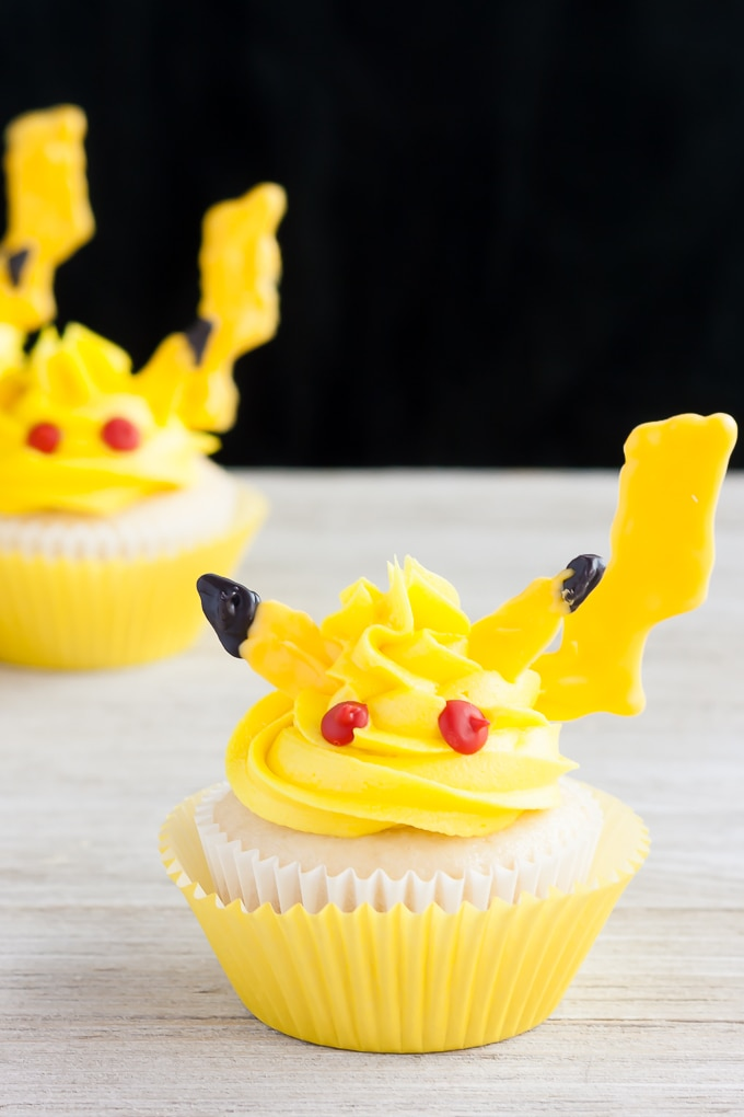 Pikachu Cupcakes sitting on a white table and a black background.