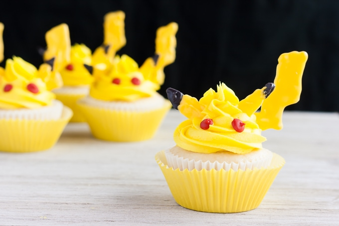 Pikachu cupcakes sitting on a white table with a black background.