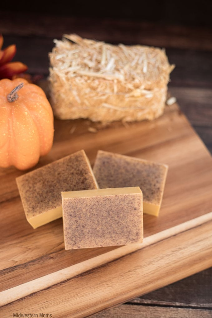 Pumpkin Pie Spice Soap sitting on a wood slab next to a mini hay bale and pumpkin.