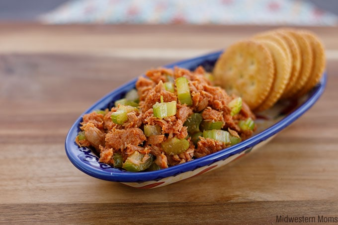 Side view of crunchy tuna sriracha in a dish with crackers on the side.
