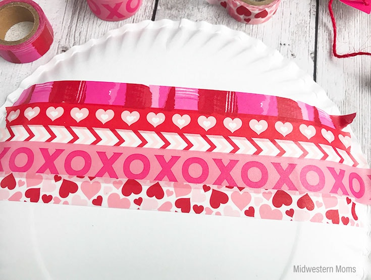 To start your valentine card, cover the back of a paper plate with washi tape.