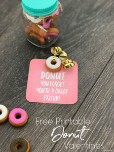 Printed Donut Valentine Card with a donut eraser attached with gold ribbon. Sitting next to a jar of donut erasers.
