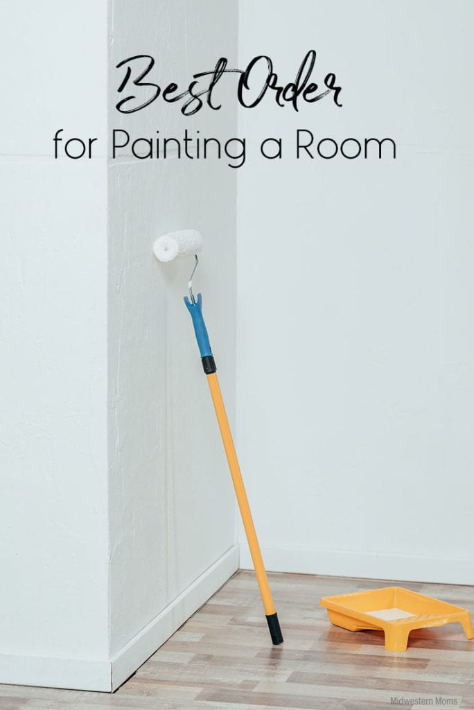 A paint roller leaning against a white wall, waiting to be used for painting.