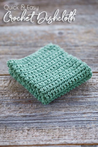 Sage Green crochet dishcloth that is folded in quarters is sitting on old barn wood background. The dishcloth is made with single crochet stitches.