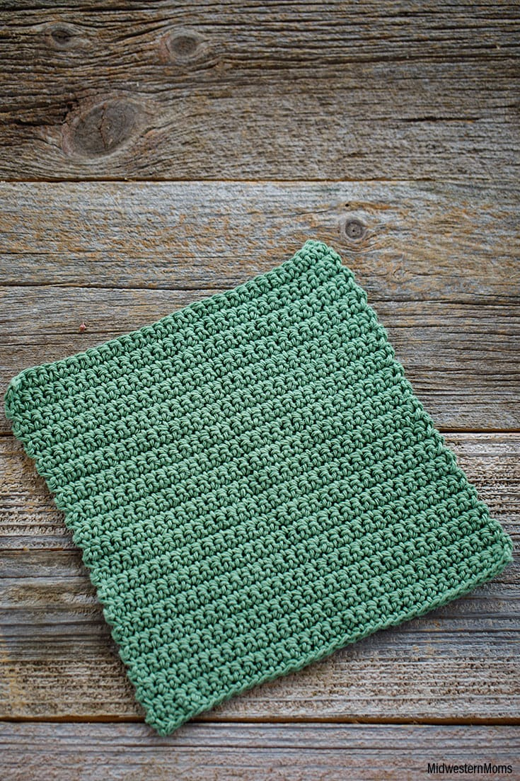 Sage green dishcloth laid flat on a barn wood background. The dishcloth is made with single crochet stitches and is perfect for beginners.
