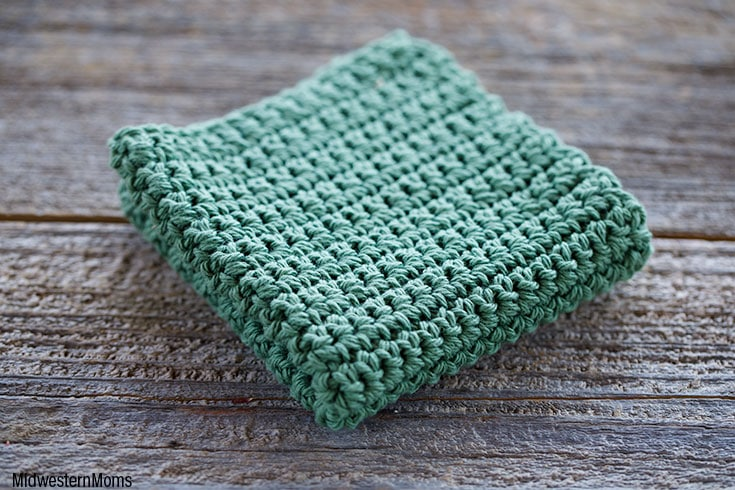 Folded crochet dishcloth on a barn wood surface.