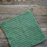 Crochet dishcloth laid out flat on old barn wood background. Dishcloth is made with single crochet stitches.