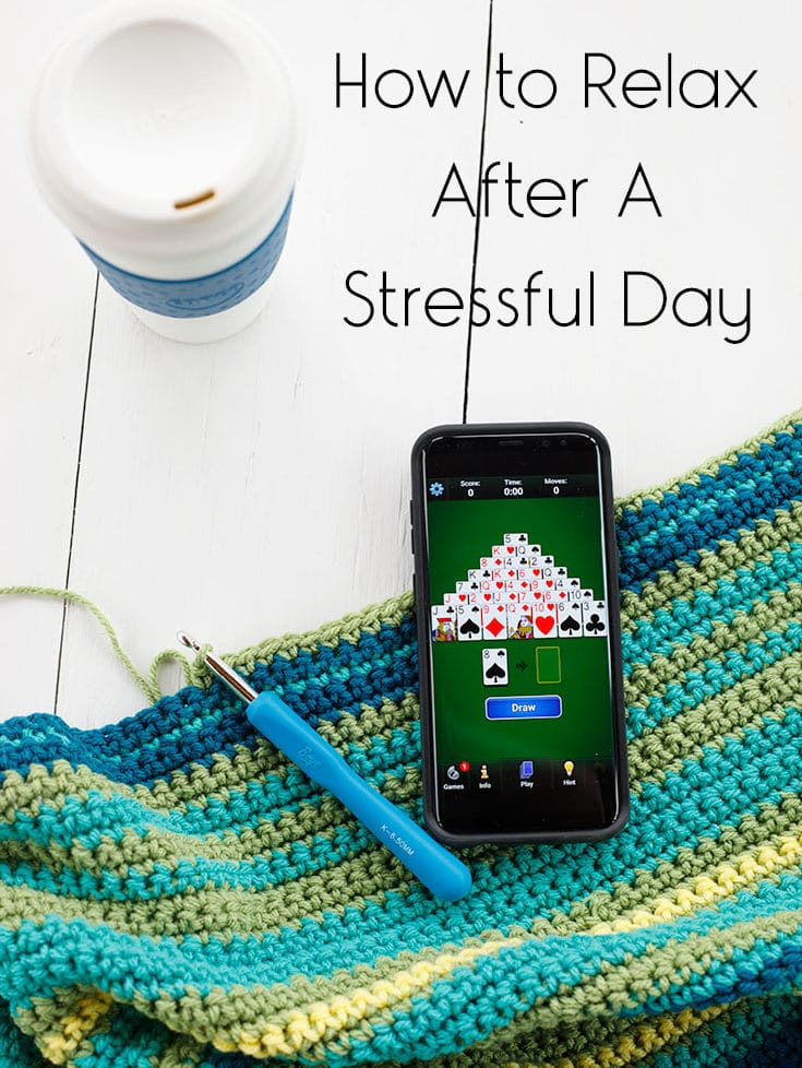 Phone showing Pyramid Solitaire game with a crochet project and a cup of tea.