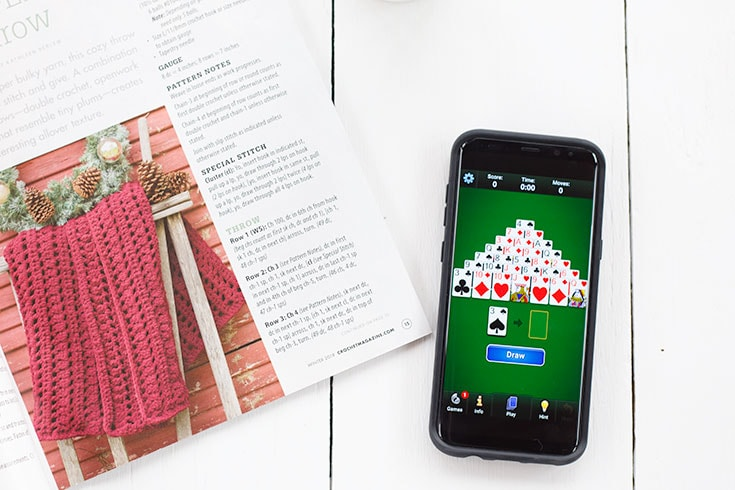 Phone showing Pyramid Solitaire Game laying next to a magazine.