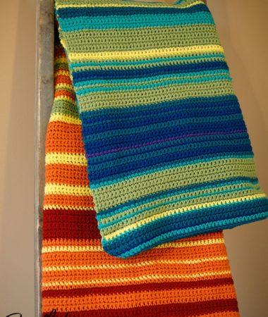 A crocheted temperature blanket draped over a blanket ladder.