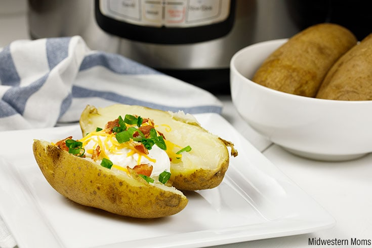 A baked potato made in an Instant Pot, shown on a white plate. Baked potato is topped with sour cream, bacon, and onions.