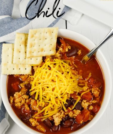 Delicious chili in a white bowl. Chili is topped with cheese and crackers and it was made in an Instant Pot.