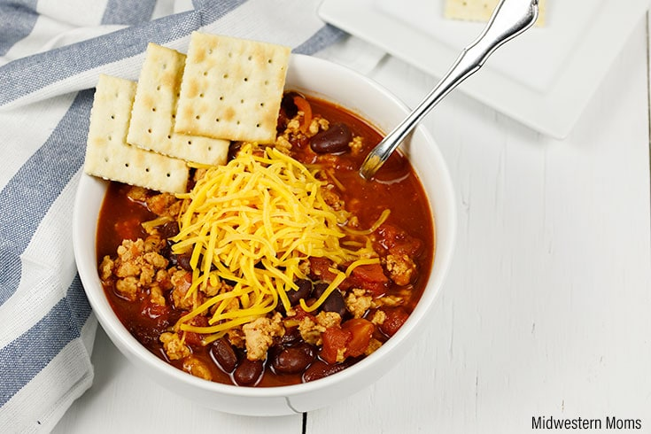 A bowl full of chili topped with shredded Cheddar cheese and saltine crackers. The chili was prepared in the instant pot.