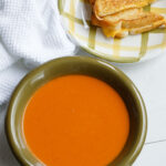 Bowl of homemade tomato soup with a grilled cheese sandwich