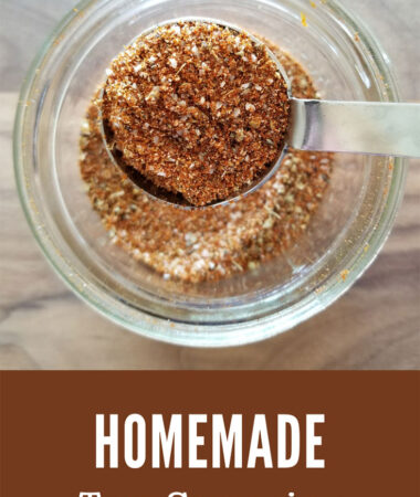 glass jar with taco seasoning with a close up of the seasoning in a tablespoon