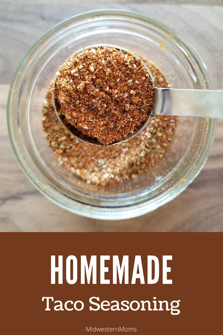 glass jar with homemade taco seasoning with a close up of the seasoning in a tablespoon
